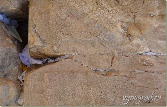 На снимке видны Молитвенные записочки людские, оставленные ими в Иерусалимской Стене Плача...